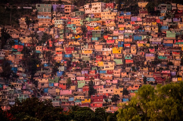 "One of Haiti's biggest shantytowns, a vast expanse of cinderblock homes on a mountainside in the nation's capital got a makeover. Workers painted a rainbow of colors on the facades of the buildings in Jalousie slum. The $1.4 million effort titled ""Beauty versus Poverty: Jalousie in Colors"" is part of a government project to relocate people from the displacement camps that sprouted up after Haiti's 2010 earthquake. Photo by Ami Vitale"