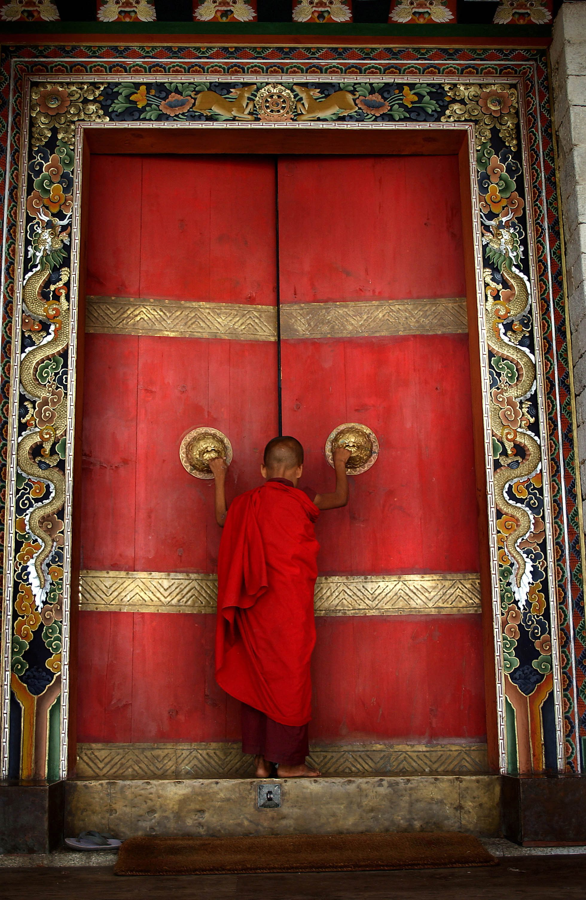 "BHUTAN:THE LAST SHANGRI LA 2: A Buddhist monk enters the formidable doors of Trongsa Dzong, the Ancestral home of BhutanÕs monarchy. The Himalayan kingdom of Bhutan has sat in isolation for thousands of years and only recently has been thrust into the glare of modern times after centuries of solitude. Bhutan is a tiny, remote, and impoverished country wedged precariously between two powerful neighbors, India and China. Violent storms coming off the Himalaya gave the country its name, meaning ""Land of the Thunder Dragon."" This conservative Buddhist kingdom high in the Himalaya had no paved roads until the 1960s, was off-limits to foreigners until 1974, and launched television only in 1999 ."